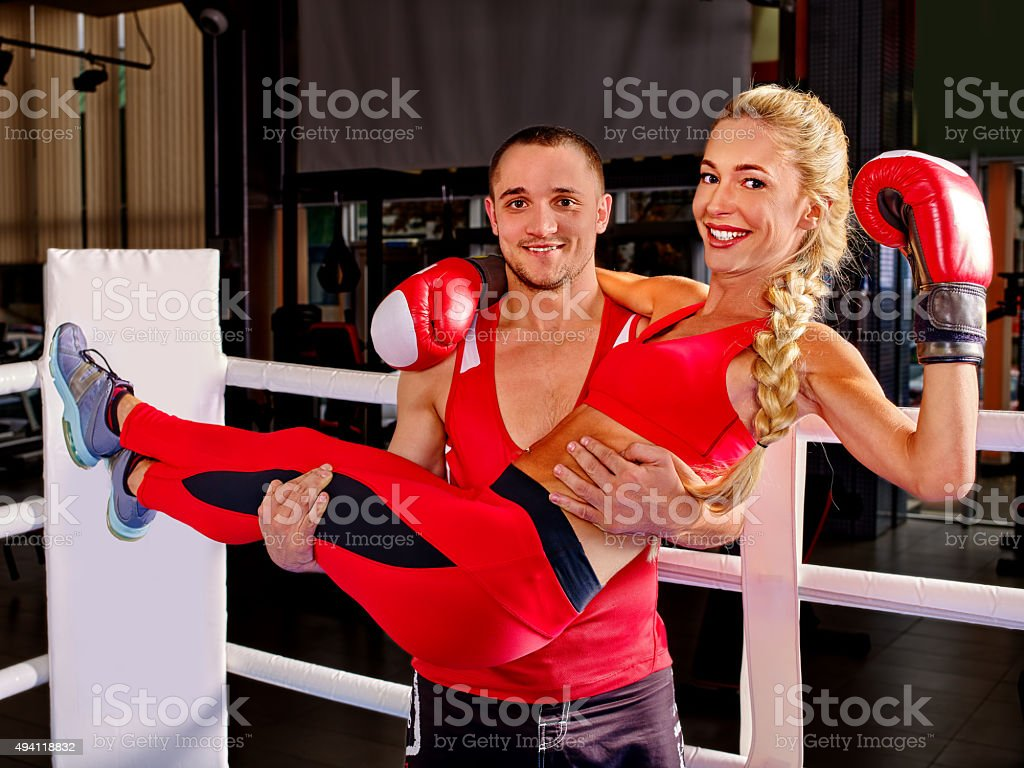 Female boxer with your male coach after workout. Man carry stock photo