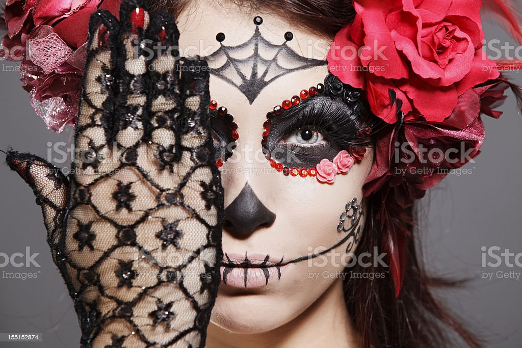 Female brunette in scary makeup acknowledges Day of the Dead stock photo