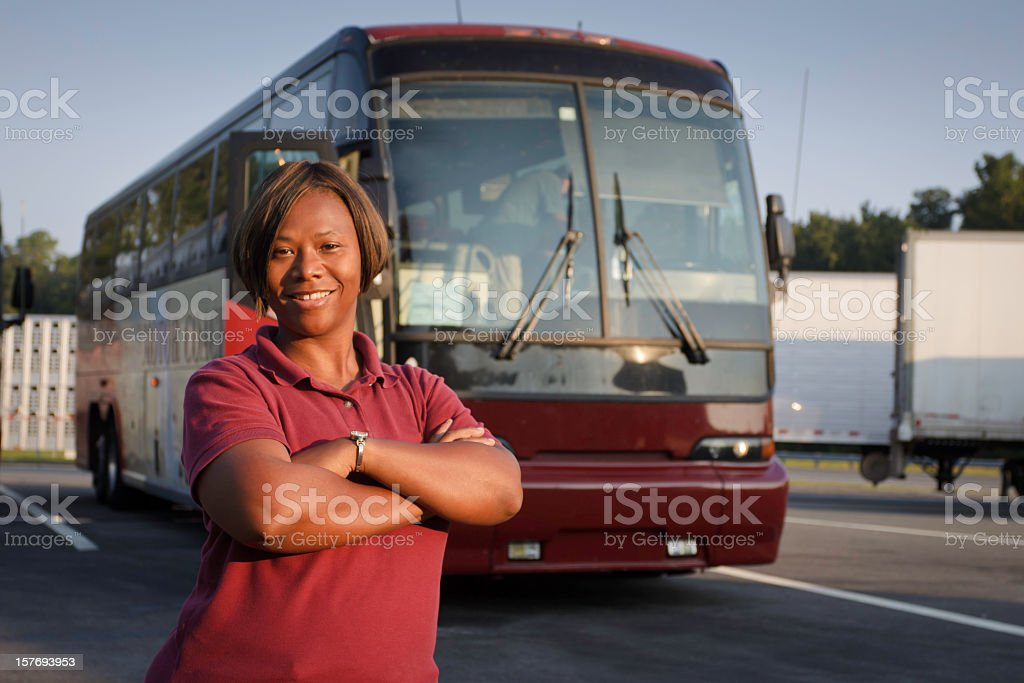 Female bus driver standing in front of a passenger bus  stock photo
