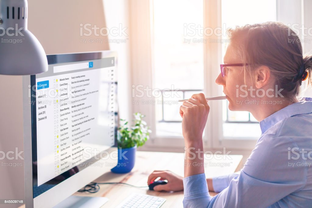 Female business person reading email on computer screen at work stock photo