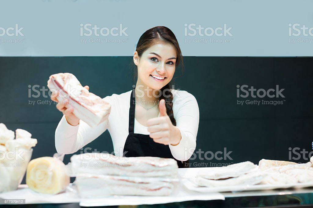 Female butcher with salty lard stock photo