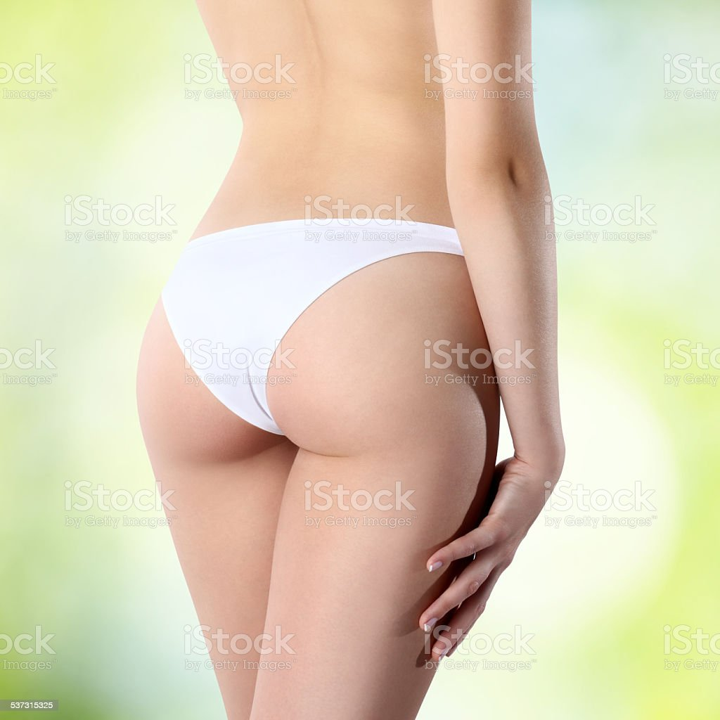 female buttocks in white panties on a green background stock photo