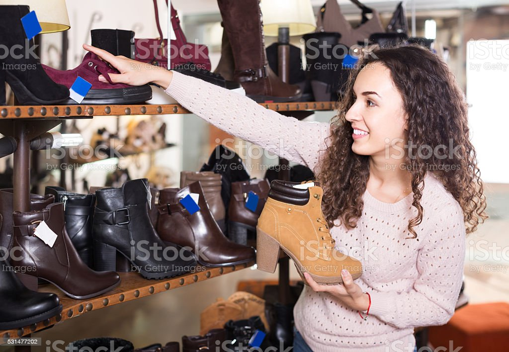 female buying winter female shoes in  shoe store stock photo