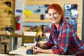 Female cabinet maker or carpenter building something in workshop
