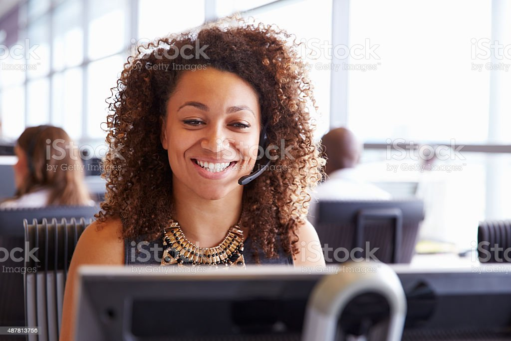 Female call centre worker, looking at screen, close-up stock photo