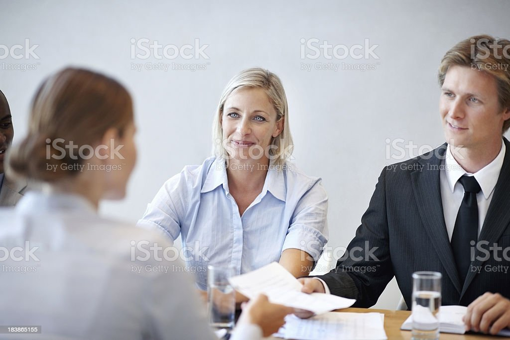 female candidate handing over her resume during interview stock