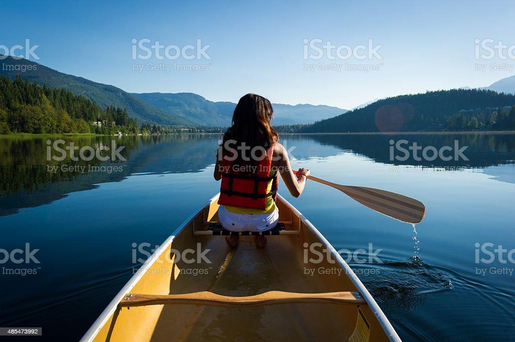Female canoeing on a prisitine lake stock photo