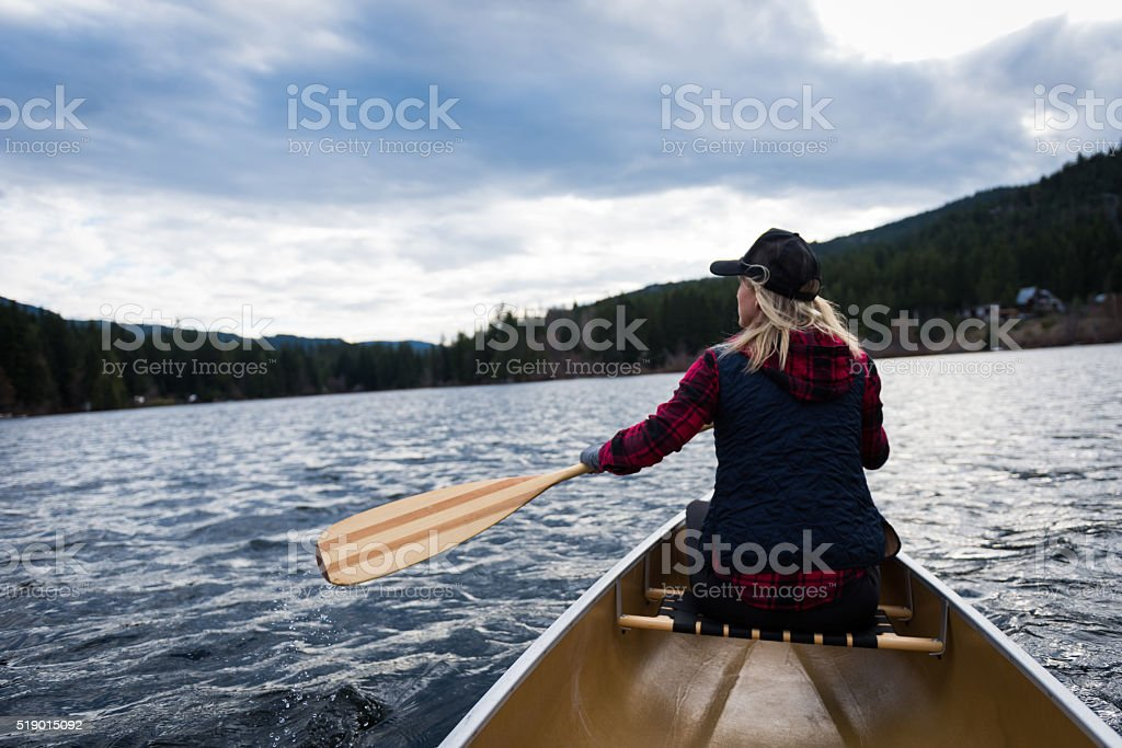 Female canoeing on a prisitine lake stock photo
