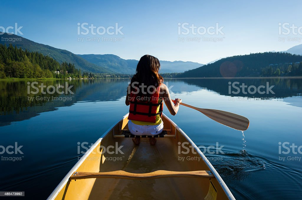 Female canoeing on a pristine lake stock photo