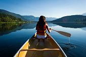 Female canoeing on a pristine lake