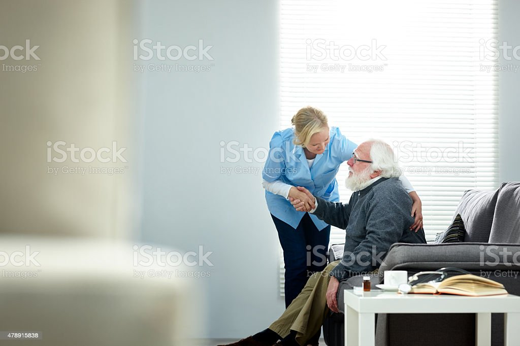 Female caregiver helping senior man get up from couch stock photo