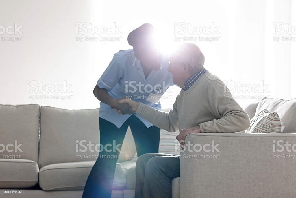 Female caregiver helping senior man get up from sofa stock photo