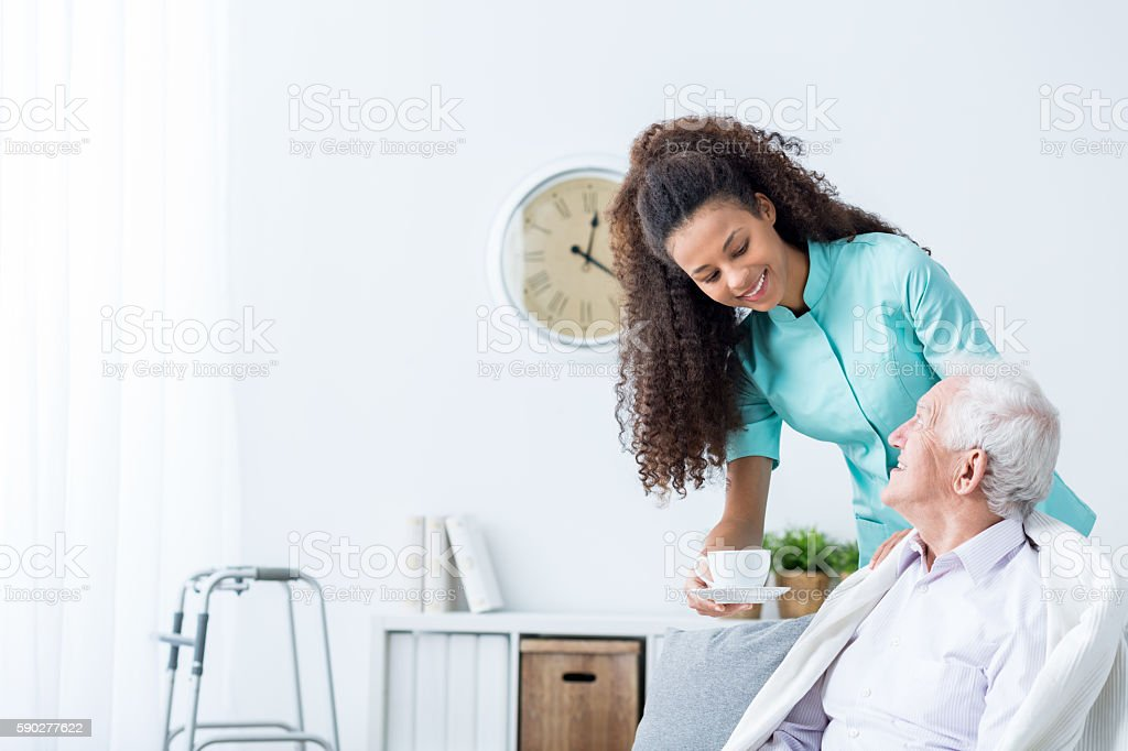 Female caregiver serving afternoon tea to patient stock photo