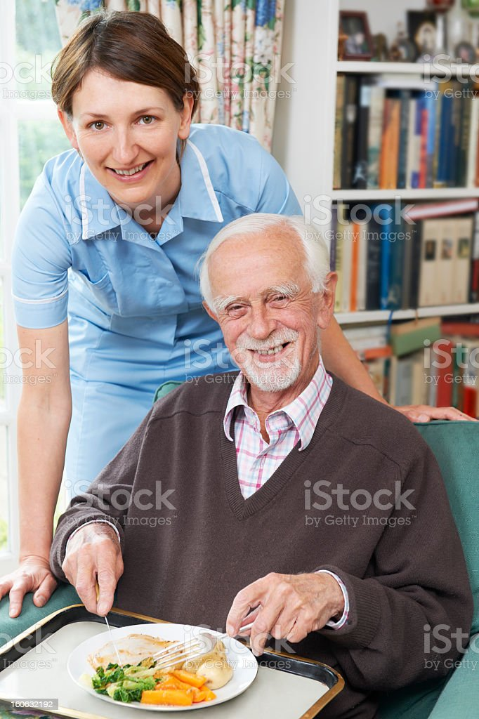 Female caretaker serving lunch to a senior man stock photo
