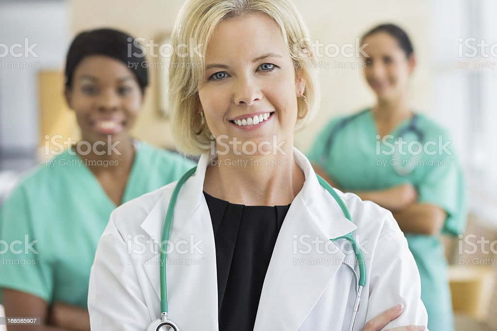 Female caring doctor with nurses stock photo
