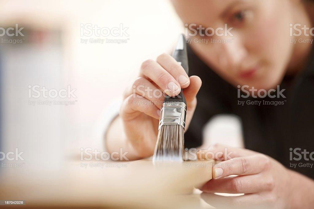 Female carpenter applying wood stain stock photo