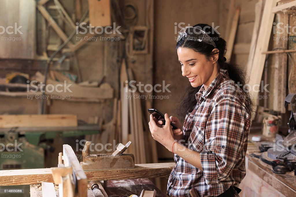 Female carpenter in workshop using on the phone stock photo