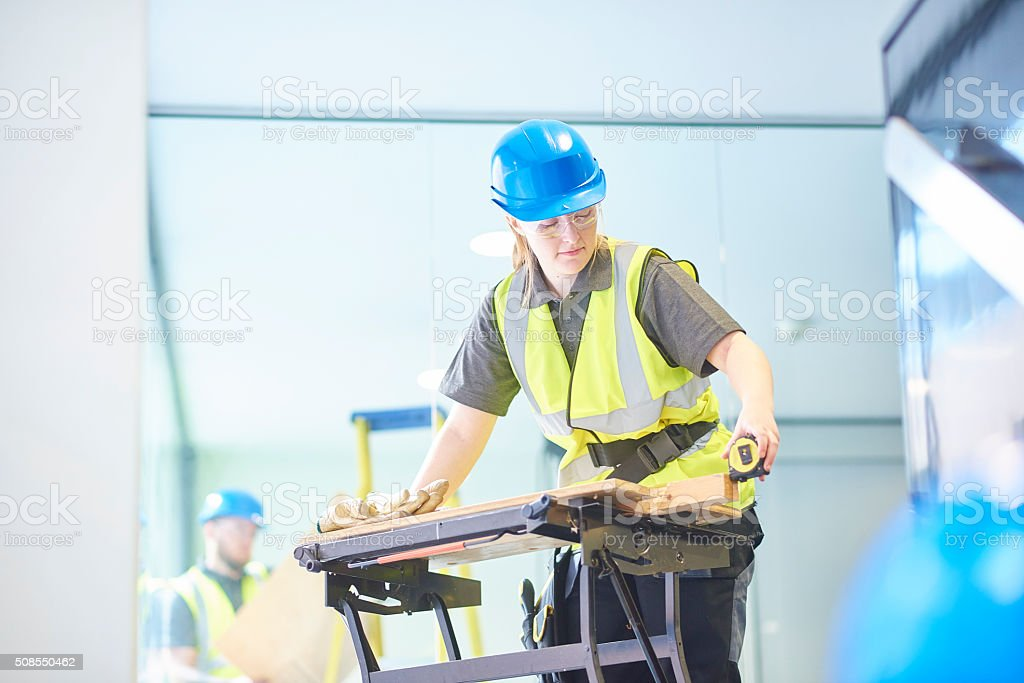 female carpenter is measuring up stock photo