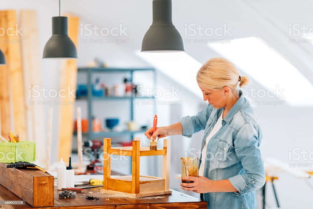 Female Carpenter Painting Furniture. stock photo