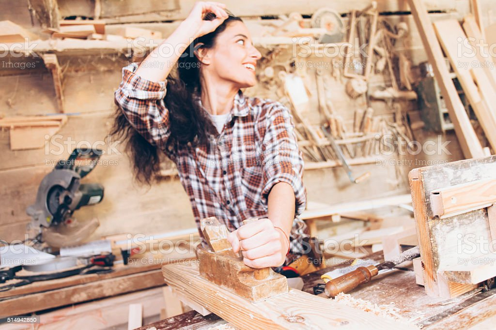 Female carpenter planing wood with a planer at work site stock photo