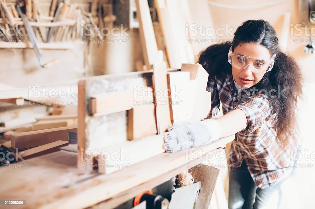 Female carpenter planing wood with at work site stock photo