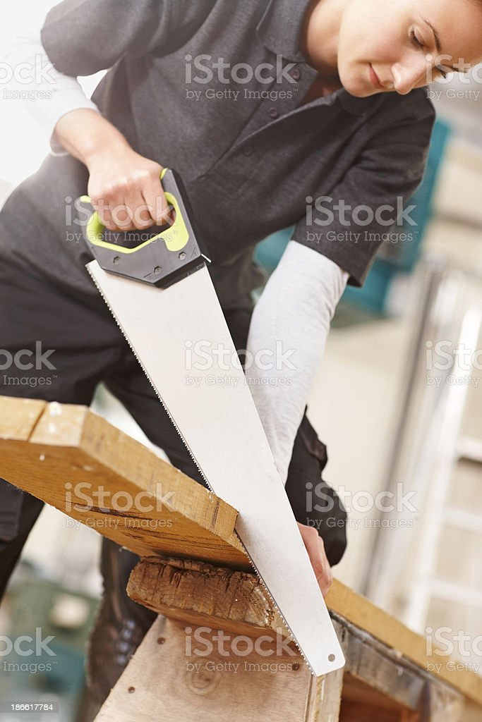 Female carpenter sawing wooden plank royalty-free stock photo
