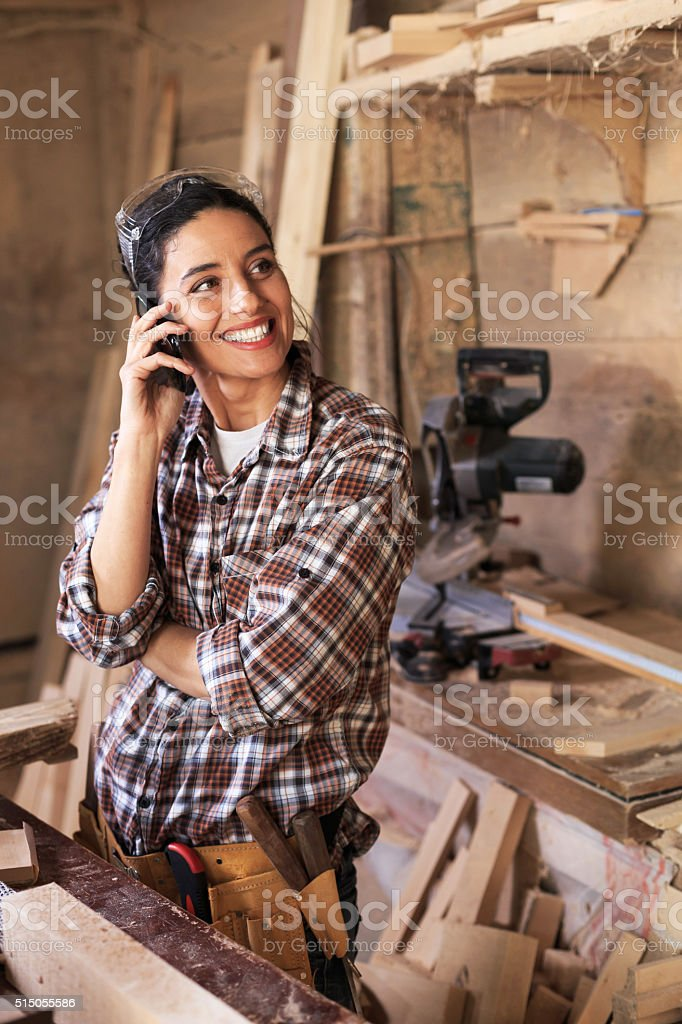 Female carpenter talking on the phone stock photo