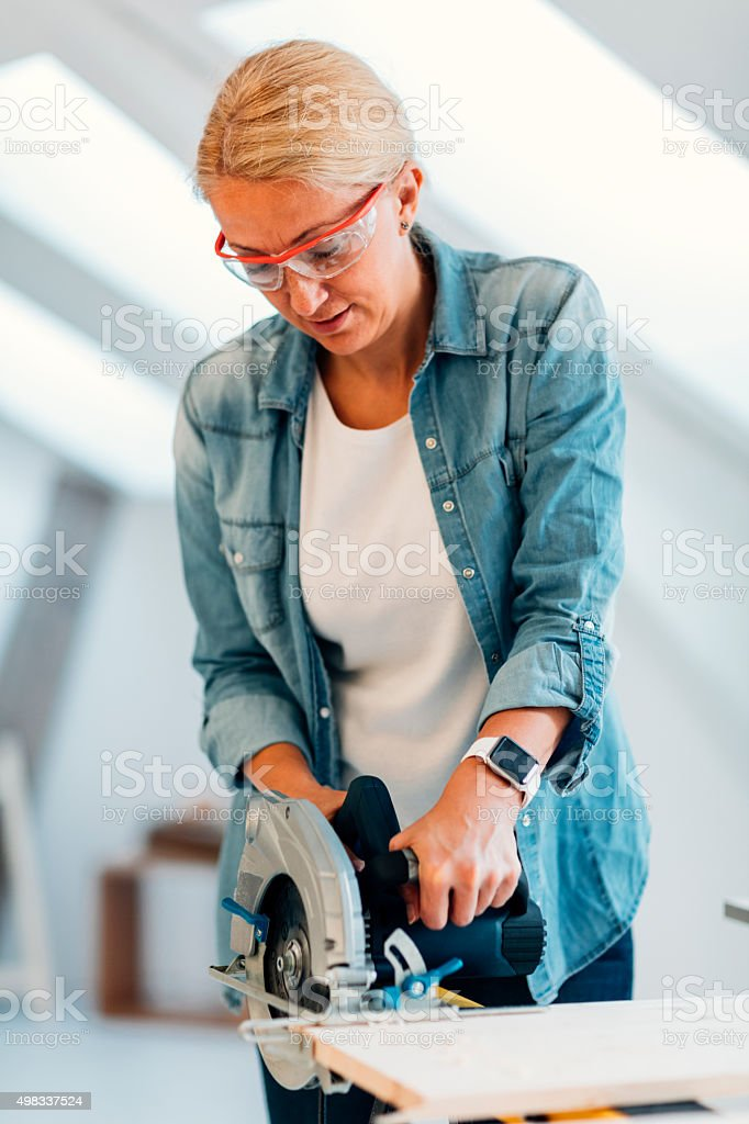 Female Carpenter Using Circular Saw. stock photo