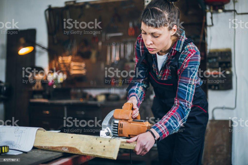 Female carpenter using circular saw stock photo