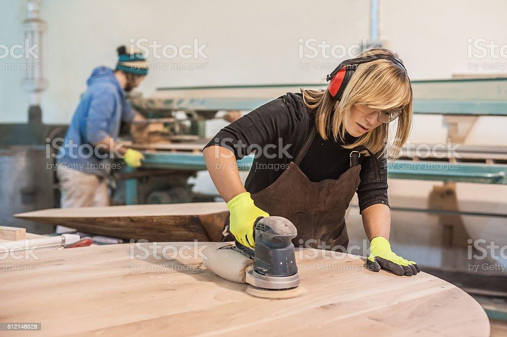 Female carpenter Using Electric Sander stock photo