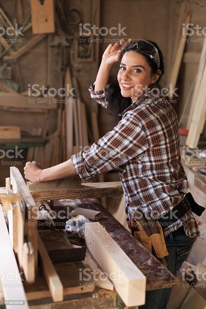 Female carpenter working in workshop stock photo