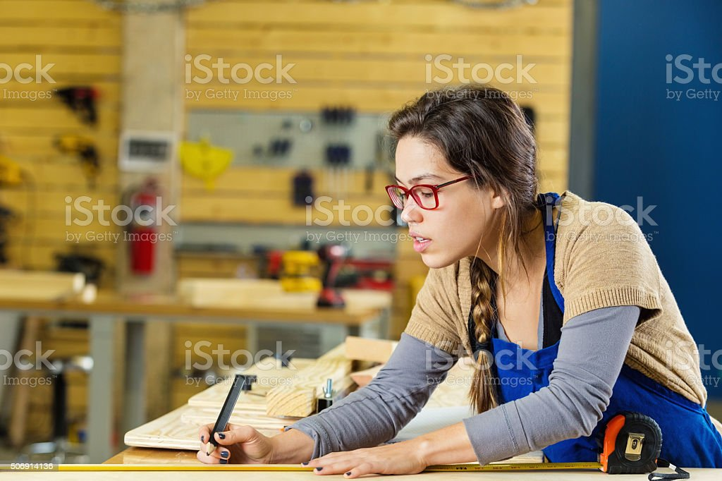 Female carpentry apprentice measuring boards in professional workshop or makerspace stock photo