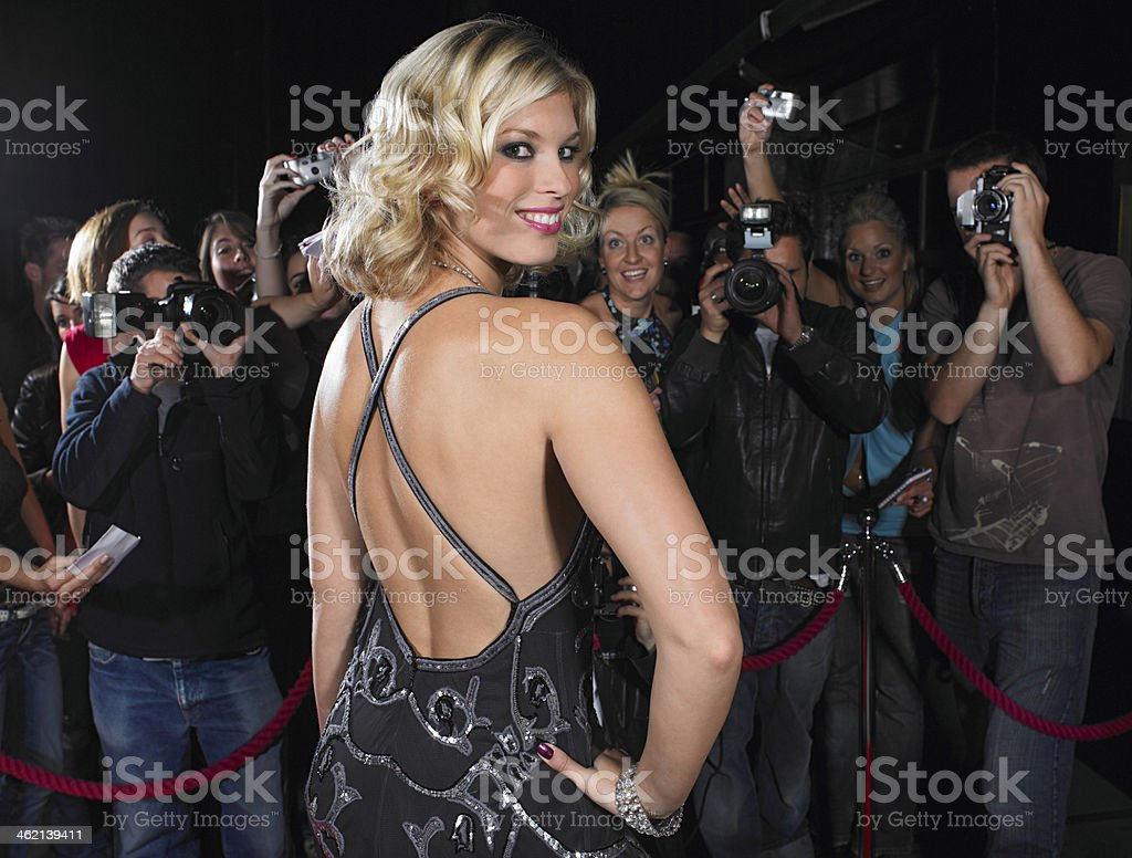 Female Celebrity Posing In Front Of Fans And Paparazzi stock photo
