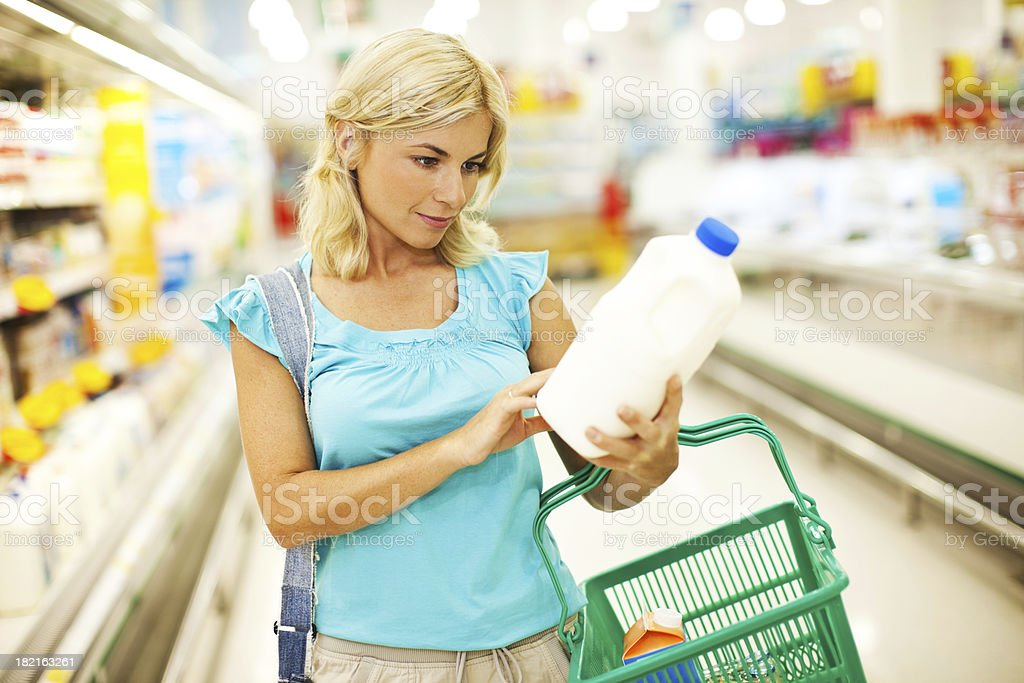 Female checking milk's labeling in supermarket. royalty-free stock photo