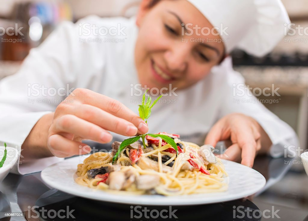 Female Chef Completing Pasta stock photo