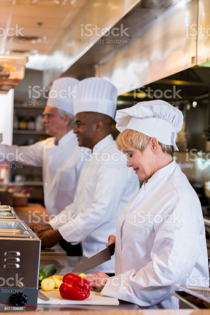 Female chef concentrates while preparing food in restaurant stock photo