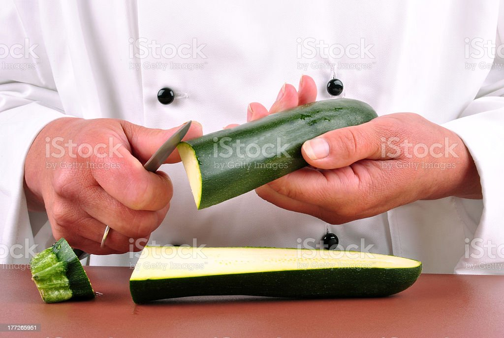 female chef cut one zucchini with a kitchen knife stock photo