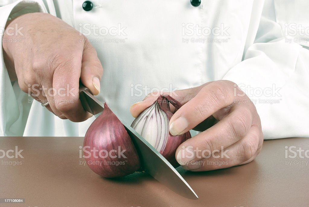 female chef cuts an lilac onion with a kitchen knife stock photo