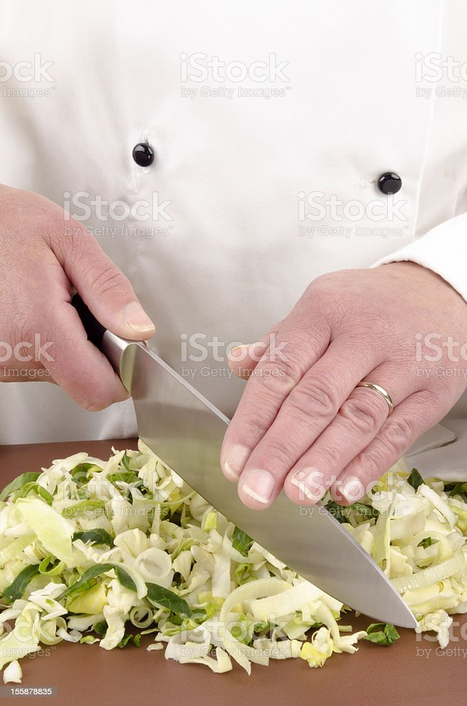 female chef cuts cabbage with a large knife stock photo