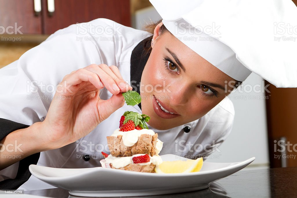 female chef decorating food in kitchen stock photo