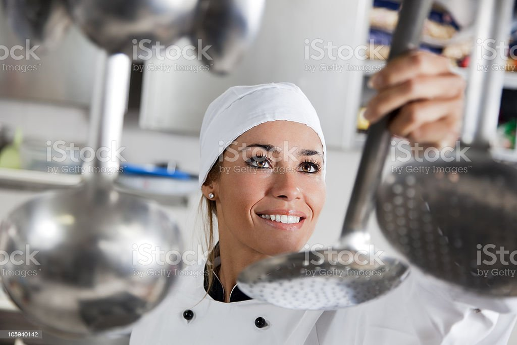 A female chef getting a utensil in the kitchen royalty-free stock photo