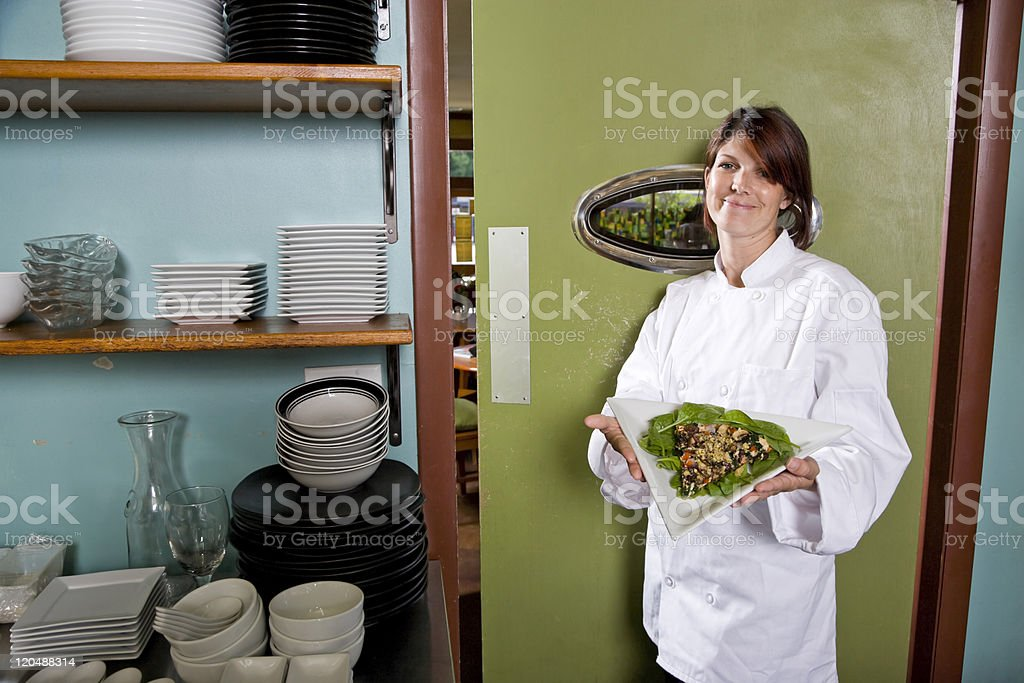 Female chef in restaurant with salad plate royalty-free stock photo