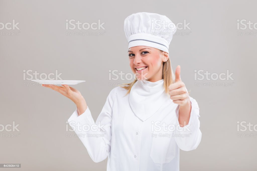 Female chef is holding plate and showing thumb up stock photo