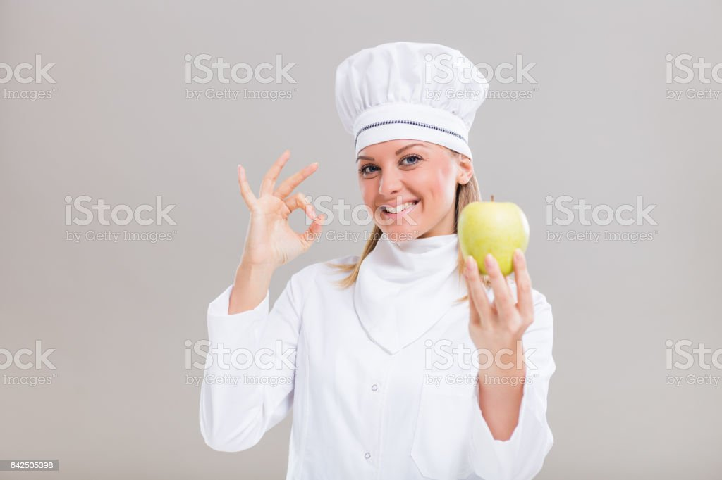 Female chef is showing ok sign and apple stock photo