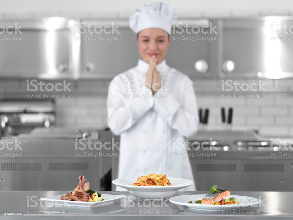 Female chef looking at delicious dishes with hands clasped stock photo