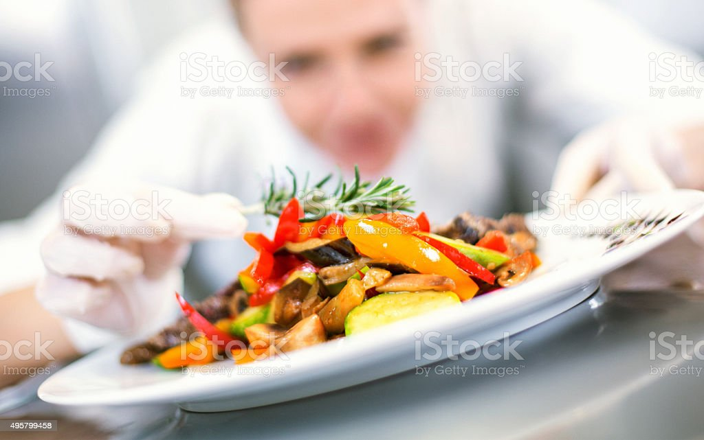 Female chef places finishing touches on meal. royalty-free stock photo
