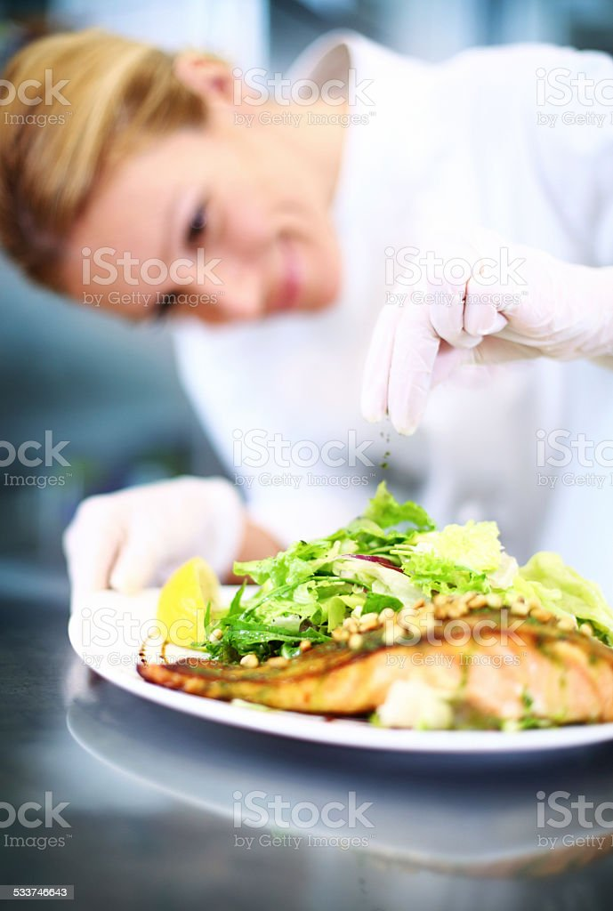 Female chef places finishing touches on meal. stock photo