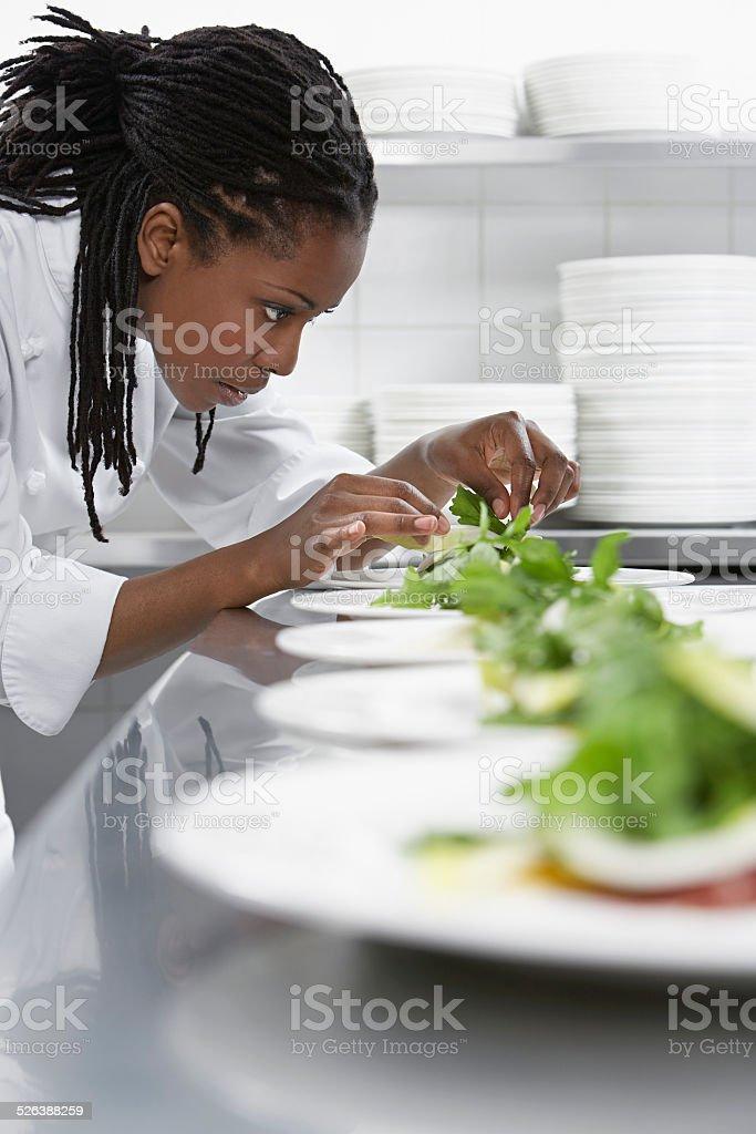 Female Chef Preparing Salad In Kitchen stock photo