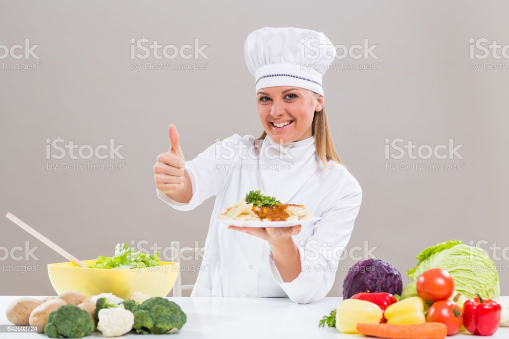 Female chef showing prepared meal and thumb up stock photo