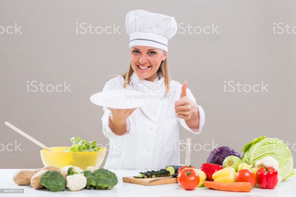 Female chef showing thumb up and empty plate stock photo